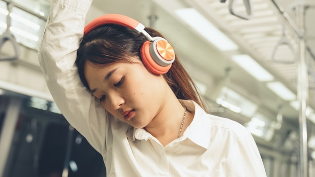 Young woman using headphones on public train