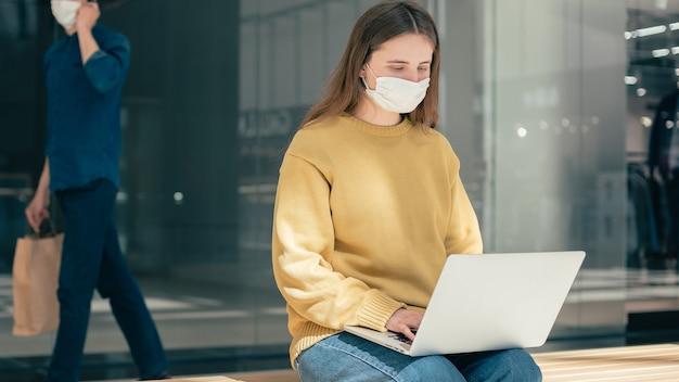 検疫中に路上で彼女のラップトップを使用して若い女性