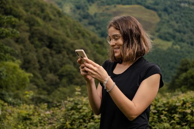 自然の中で彼女の携帯電話を使用して若い女性