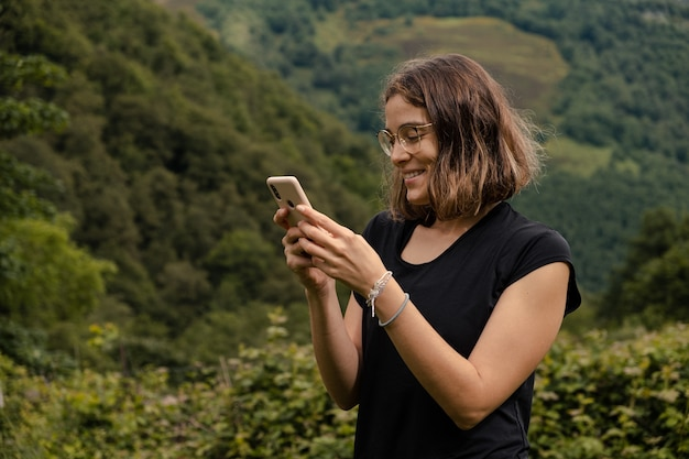 Giovane donna che utilizza il suo telefono cellulare nella natura