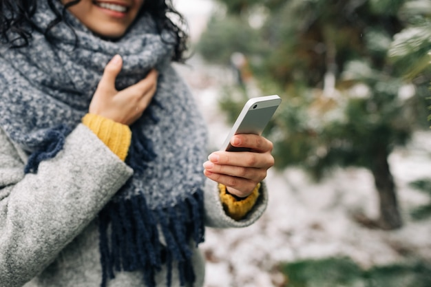 Young woman using her mobile phone at a snowy winter park. closeup of female checking news and texting on her cellphone outdoor during cold winter season. peoples' gadgets concept.