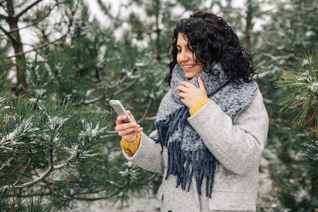 Young woman using her mobile phone at a snowy winter park. peoples' gadgets concept.