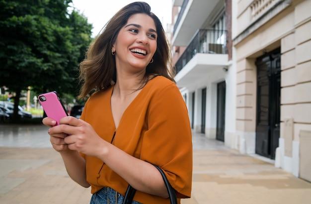路上で屋外に立っている間彼女の携帯電話を使用して若い女性。都市とコミュニケーションの概念。