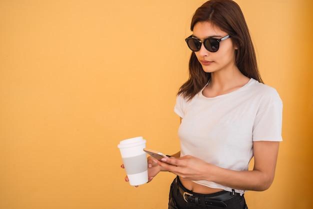 若い女性が彼女の携帯電話を使用しています。