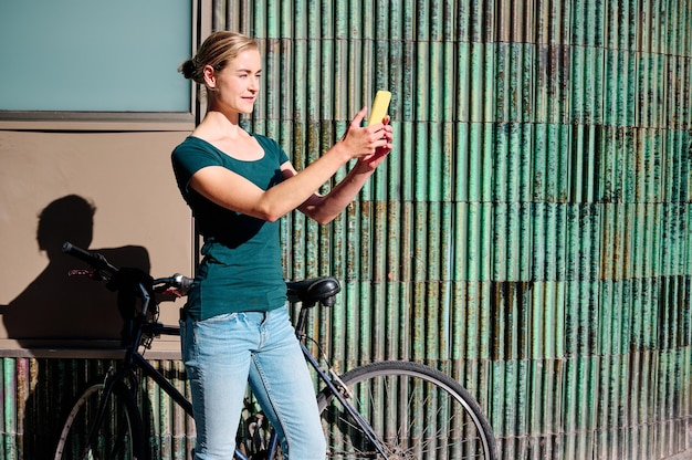 Young woman using her smarpthone outdoors with her bike