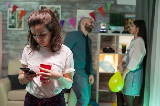 쾌활한 파티에서 스마트폰을 사용하는 젊은 여성. 남자와 여자는 백그라운드에서 얘기입니다.