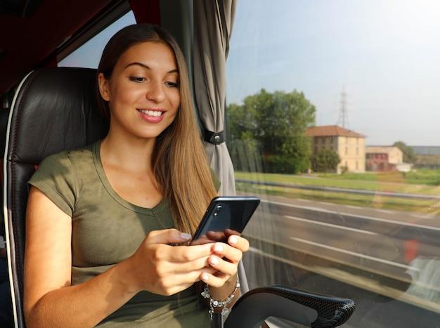 버스에서 그녀의 스마트 폰을 사용 하여 젊은 여자. 여행 개념에 사람들이 기술.