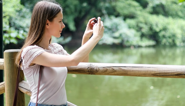 Young woman using her smartphone outdoor in a park and taking pictures