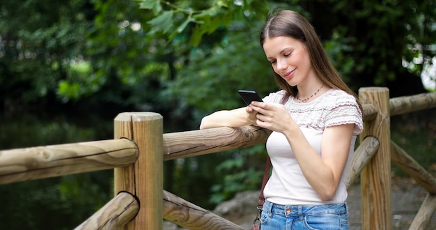 Young woman using her smartphone in a park