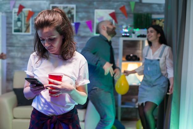 친구들이 배경에서 축하하고 춤을 추는 동안 스마트폰을 사용하는 젊은 여성.