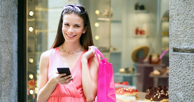 Young woman using her smartphone while shopping in a city