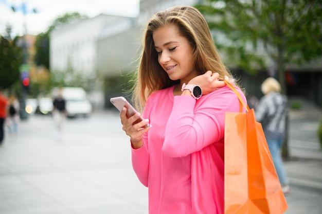 도시에서 쇼핑하는 동안 그녀의 스마트 폰을 사용하는 젊은 여자