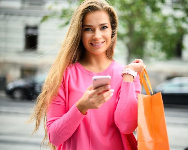 街で買い物をしながらスマートフォンを使用する若い女性
