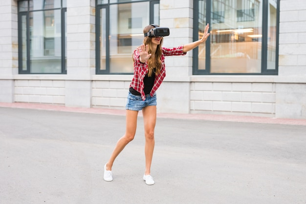 Young woman using high tech virtual reality glasses outdoor