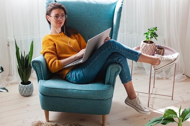 自宅の肘掛け椅子に横たわっている間ラップトップとヘッドフォンを使用して若い女性