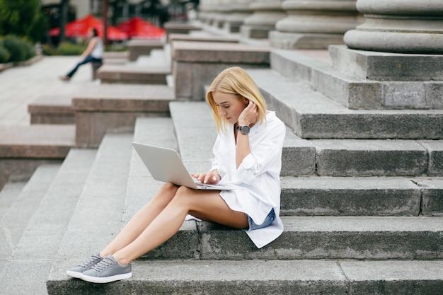 Молодая женщина, используя портативный компьютер и смартфон. красивая студент девушка, работающих на ноутбуке на открытом воздухе