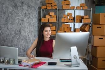 ラップトップコンピュータを使用している若い女性。起業家はビジネスを成功させる。出荷Onlin