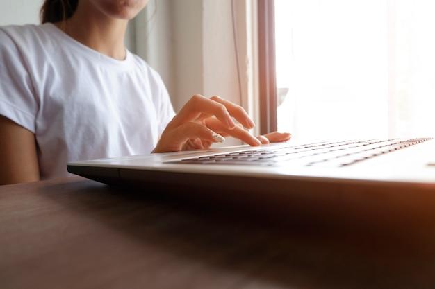 Молодая женщина, используя портативный компьютер, сидя в кафе, вспышки вс