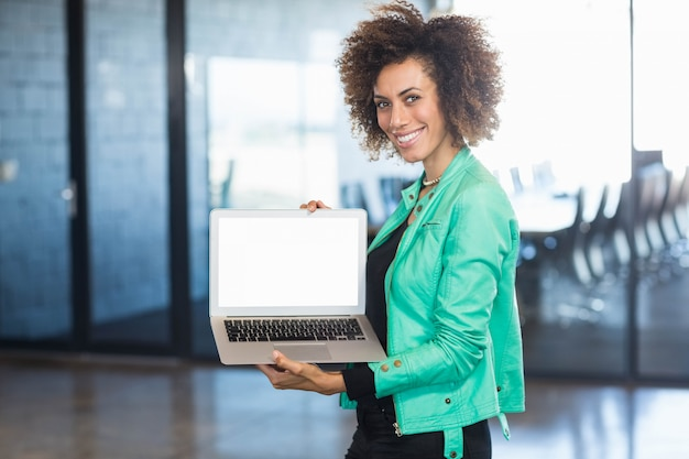 Young woman using laptop in front of conference room in the office