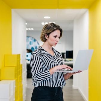Молодая женщина, используя ноутбук в зале офиса