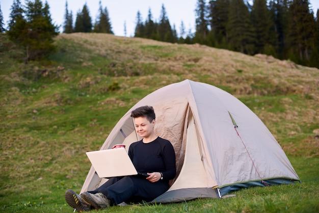 ラップトップを屋外で使う若い女性