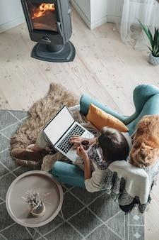 아늑한 안락의자에 랩탑 스크린 모형을 사용하고 집에서 차를 마시며 집에서 고양이와 함께 벽난로 옆에 격자 무늬로 앉아 있는 젊은 여성