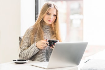 Young woman using laptop sitting with cup