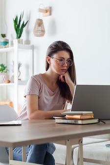 自宅で仕事をするためにラップトップを使用して若い女性
