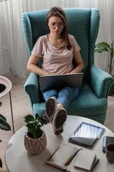 집에서 일하기 위해 노트북을 사용하는 젊은 여성, 원격 작업