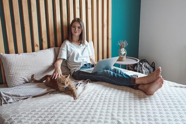 집에서 애완용 고양이와 함께 침대에 누워 일하기 위해 노트북을 사용하는 젊은 여성. 탄력근무제와 원격근무