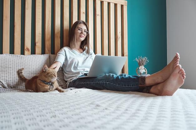 노트북을 사용하여 침실에 애완 고양이와 함께 침대에 누워 있는 젊은 여성. 탄력근무제와 원격근무.
