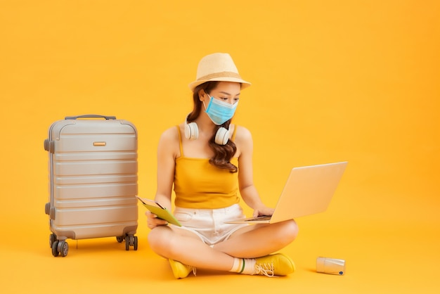 オレンジ色の背景の上に彼女のスーツケースで飛行を待っている間、ラップトップを使用して、フェイスマスクを身に着けている若い女性。