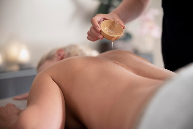 Young woman using massage oil on her client