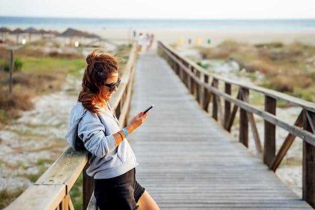 해안 지역에서 모바일 휴대 전화를 사용 하여 젊은 여자.