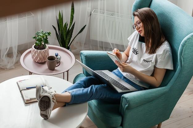 휴대 전화 및 노트북을 사용 하여 젊은 여자