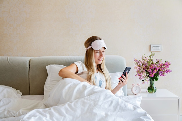 Young woman using mobile phone on the bed