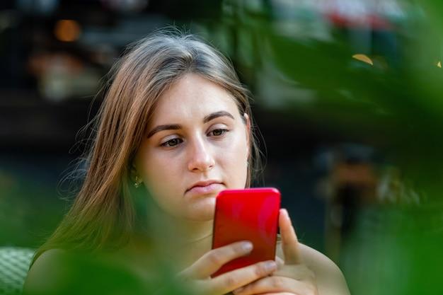 携帯電話、コミュニケーション、デジタル画面を見て、屋外カフェに座っている若い女性
