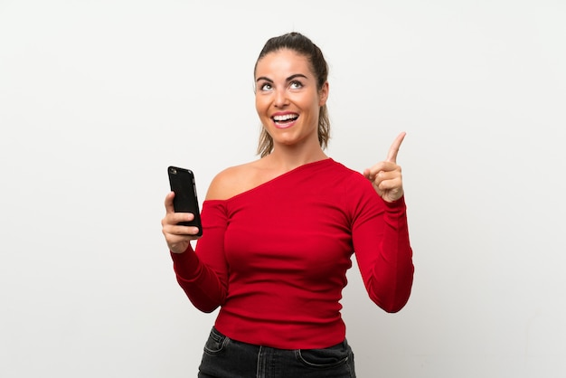 Young woman using mobile phone intending to realizes the solution while lifting a finger up