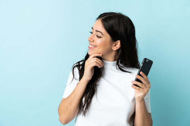 Young woman using mobile phone isolated on blue background thinking an idea and looking side