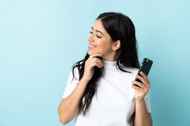 아이디어를 생각하고 측면을 찾고 파란색 배경에 고립 된 휴대 전화를 사용하는 젊은 여자