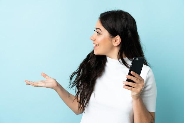 Молодая женщина, использующая мобильный телефон, изолирована на синем фоне с удивленным выражением лица