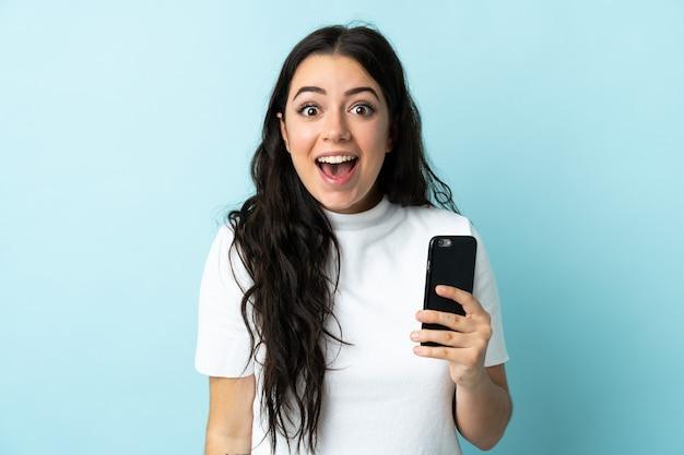 놀람과 충격 된 표정으로 파란색 벽에 고립 된 휴대 전화를 사용하는 젊은 여자