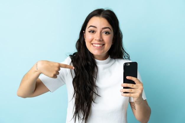 Молодая женщина, использующая мобильный телефон, изолирована на синем с удивленным выражением лица