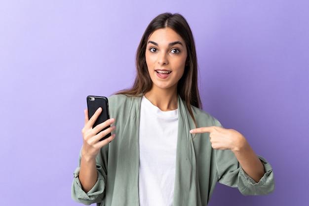 Молодая женщина, использующая мобильный телефон, изолирована на фиолетовой стене с удивленным выражением лица