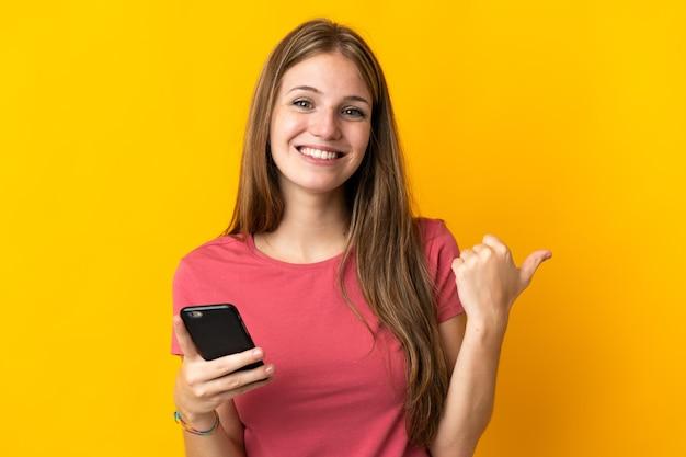 製品を提示するために側面を指している黄色の壁に分離された携帯電話を使用して若い女性