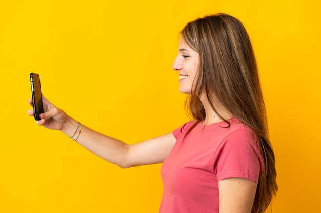 Молодая женщина с помощью мобильного телефона изолирована на желтой стене со счастливым выражением лица