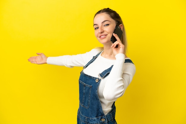 Young woman using mobile phone over isolated yellow background extending hands to the side for inviting to come