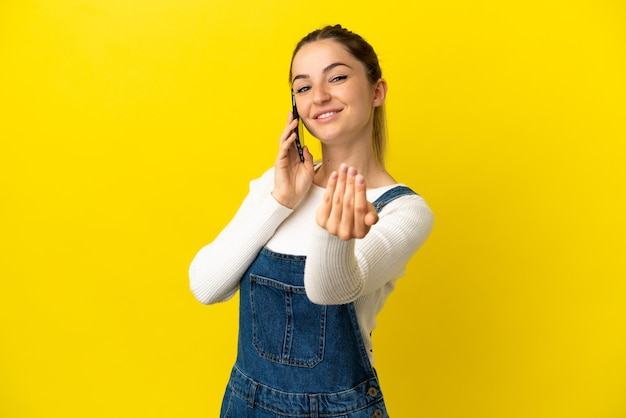 Young woman using mobile phone over isolated yellow background inviting to come with hand. happy that you came