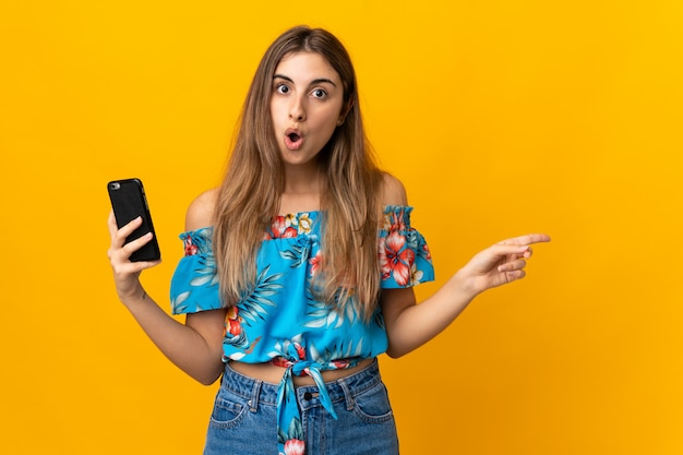 Young woman using mobile phone over isolated yellow wall surprised and pointing side