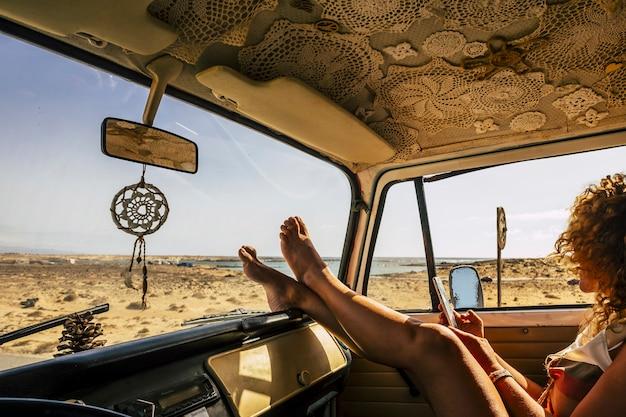 ダッシュボードに足で車に寄りかかって携帯電話を使用して若い女性。女性のテキストメッセージ携帯電話。ロードトリップを楽しんでいます。ダッシュボードに足を置きながら電話を使用して車に座っている女性観光客